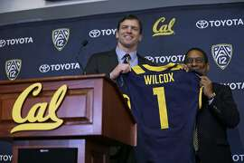 California head football coach Justin Wilcox, left, is presented a jersey by Director of Athletics Mike Williams, right, during a news conference Tuesday, Jan. 17, 2017, in Berkeley, Calif. California officially introduced Wilcox, hoping the long-time defensive coordinator can help revive the struggling program. (AP Photo/Eric Risberg)