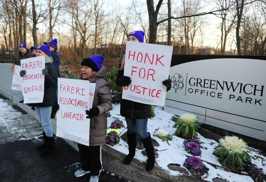 Indiana Y. Pena, left, of Port Chester, N.Y., Rosa Vasquez, center, of Stamford, and Mayra Maurad, of Port Chester, N.Y., hold up sign in protest outside Greenwich Office Park in Greenwich, Conn. Monday, Jan. 16, 2017. Former cleaners at Greenwich Office Park are demanding that Fareri Associates reinstate the 11 employees whom the building owners displaced from their jobs. On Nov. 4, the building owners ended their relationship with a cleaning contractor and did not rehire many of the workers left without jobs. The National Labor Relations Board is now investingating Fareri Associates for unfair labor practices. Photo: Tyler Sizemore / Hearst Connecticut Media / Greenwich Time