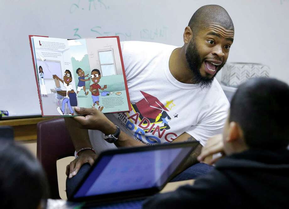 "Former NFL player Wade Smith reads from his book, ""Smitty Hits The Play Books,"" to a group of third graders at Browning Elementary Tuesday. Smith helped launch the My Home Library program, created by the Barbara Bush Houston Literacy Foundation. Photo: Melissa Phillip, Houston Chronicle / © 2017 Houston Chronicle"