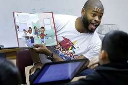 Former NFL player Wade Smith reads from his book titled Smitty Hits The Books to a group of third graders at Browning Elementary, 607 Northwood St., Tuesday, Jan. 17, 2017, in Houston. The event with the Wade Smith Foundation, the Barbara Bush Houston Literacy Foundation and the Superbowl Host Committee was a kick-off of the My Home Library program that lets kids create an online wish list of five books. Then for a $30 donation, people can purchase those books for a child's home library.