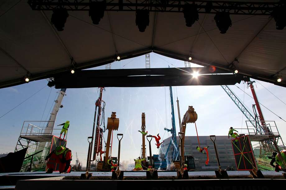 FILe-- Performers at the end of the ceremony do acrobatics against the building site of the new stadium as the NBA Golden State Warriors during a ground breaking ceremony for Chase Center.Monday and Tuesday's service interruptions on Muni's T-Third line prompted rider complaints about buses missing stops and long delays asbusesstackedup on Third Street. Photo: Michael Macor, The Chronicle