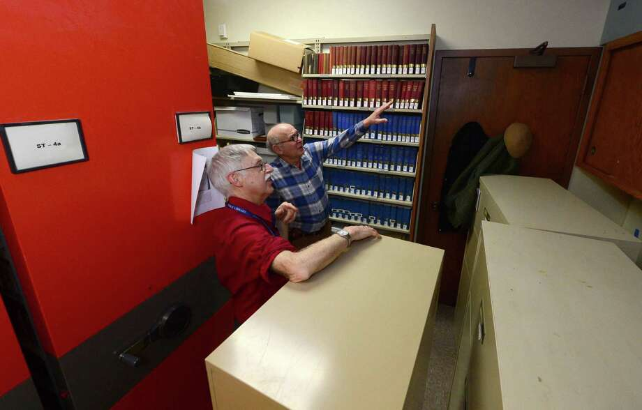 Norwalk Public Library Archival Manager Paul Keroack and volunbteer Gary Dwor-Frecault work in the Norwalk Library Main Branch's History Center Tuesday, January 17, 2017, following the flooding that closed the branch last Thursday and damaged material in the Center in Norwalk, Conn. Although the branch reopened on Friday the History Center will not be open for another 10 days. due to the fact that material is still damp and fans are set up drying the space after a water pipe broke in the ceiling of the top floor sending water downward in the building. Photo: Erik Trautmann / Hearst Connecticut Media / Norwalk Hour