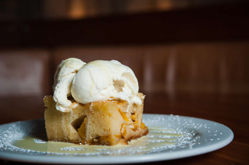 Peach Pudding Cake: Moist vanilla cake layered with peaches, served warm, topped with vanilla bean ice cream and drizzled with vanilla anglaise. All desserts are made in-house and from scratch! CLICK HERE!