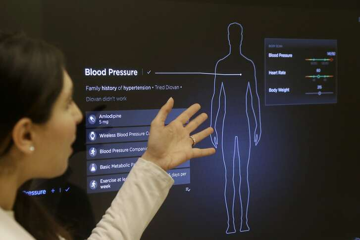 In this Jan. 10, 2017 photo, Dr. Aaliya Yaqub points to a large monitor while giving a demonstration of medical checkup at a Forward medical office in San Francisco. After a relative suffered a heart attack a few years ago, Silicon Valley entrepreneur Adrian Aoun got an up-close look at a health-care system that he diagnosed as an inefficient and outdated mess. Now, Aoun is ready to prescribe his remedy. It's called Forward, a health-management service that charges a $149 per month, roughly $1,800 a year, to tend to all of its patients' primary-care needs. (AP Photo/Jeff Chiu)