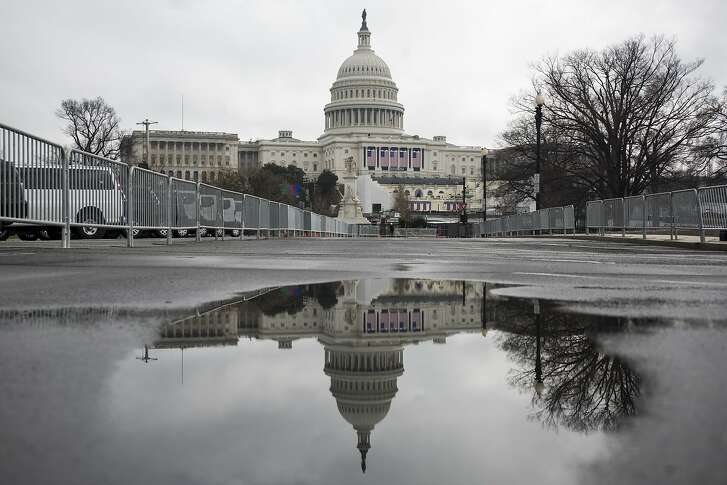 "The U.S. Capitol building is seen reflected in a puddle in Washington, D.C., U.S., on Tuesday, Jan. 17, 2017. U.S. President-elect Donald Trump plans to issue some executive orders on inauguration day and may swear in some of his cabinet members, according to Trump's spokesman Sean Spice. But the incoming president will wait until Monday, the first full business day of his presidency, for ""a big flurry of activity."" Photographer: Zach Gibson/Bloomberg"