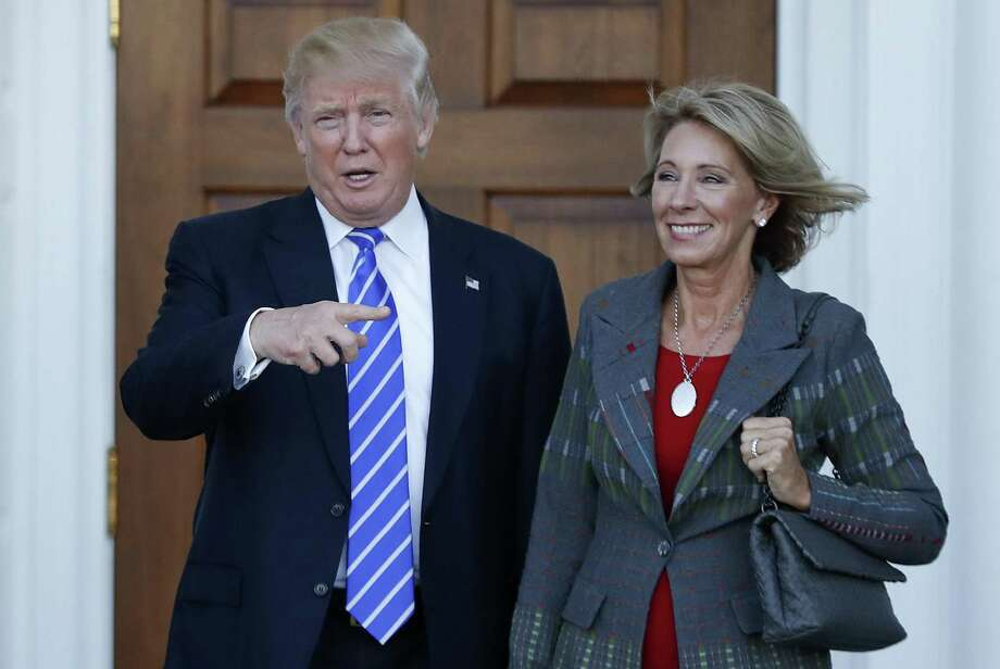 President-elect Donald Trump stands with Education Secretary-designate Betsy DeVos in Bedminster, N.J. on Nov. 19, 2016. DeVos has spent over two decades advocating for school choice programs, which give students and parents an alternative to traditional public school education. Photo: Carolyn Kaster / Associated Press / Copyright 2016 The Associated Press. All rights reserved.