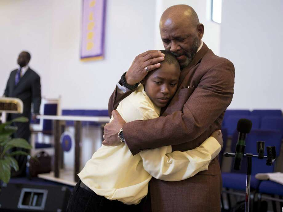 Reverend Melvin Price, right, hugs Malcolm Harvin, 11, second right, during Sunday service at Dominion Church of God in Christ on Sunday, January 8, 2016 in San Antonio, Texas. Photo: Matthew Busch, For The San Antonio Express-News / For The San Antonio Express-News / © Matthew Busch