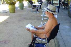 """In the nude, George Davis, 65, reads outside the entrance to the Castro BART station at the corner of 17th Street and Castro Street in San Francisco, California. Davis, who calls himself an """"urban nudist,"""" campaigned in the buff for mayor in 2007. (Maria LaGanga/Los Angeles Times/MCT)"""