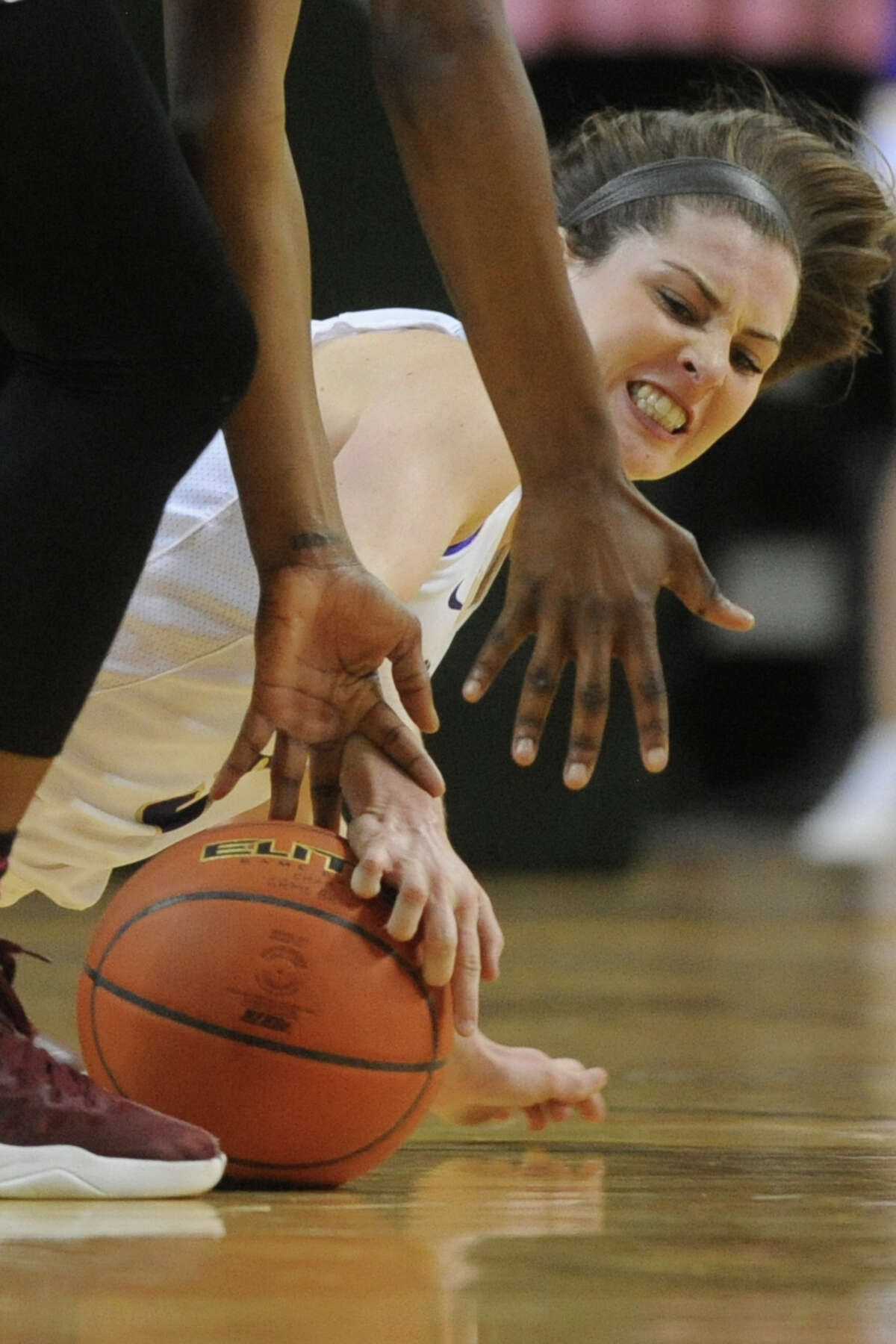 Midland High's Jayci Streun (5) reaches for a loose ball against Lee's Zion Niblett (30) on Tuesday, Jan. 17, 2017, at Chaparral Center. James Durbin/Reporter-Telegram