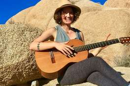 Emilie Inman, killed in a Berkeley stabbing, is seen playing guitar a few weeks ago at a campsite in Joshua Tree.