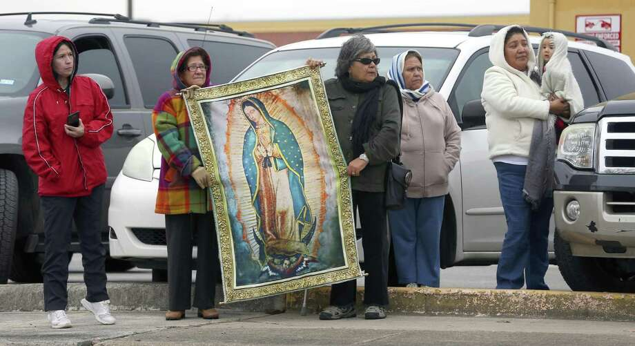 St. Ann's catholic church parishioners including Rafaela Juarec, holding the left side of the Our Lady of Guadalupe banner, and Diana estrada, holdding the right side, wait Tuesday, Jan. 17, 2017 outside San Fernando Cemetery No. 2 for Archbishop Emeritus Patrick Flores' funeral procession to pass. Photo: William Luther, Staff / San Antonio Express-News / © 2017 San Antonio Express-News
