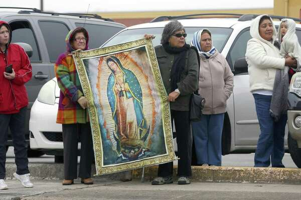 St. Ann's catholic church parishioners including Rafaela Juarec, holding the left side of the Our Lady of Guadalupe banner, and Diana estrada, holdding the right side, wait Tuesday, Jan. 17, 2017 outside San Fernando Cemetery No. 2 for Archbishop Emeritus Patrick Flores' funeral procession to pass.
