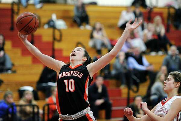 Ridgefield's Meaghan O'Hara (10) a rebound as Greenwich's Julia Conforti looks on during their game Tuesday night at Greenwich High. O'Hara scored a team-high 14 points in the Tigers' 63-51 win.