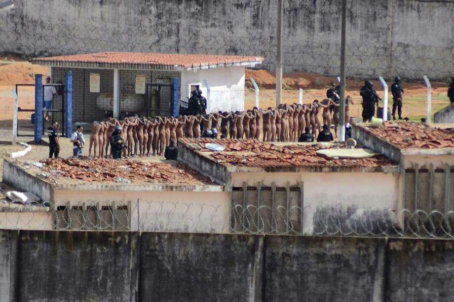 FILE - In this Jan. 15, 2017 file photo, inmates stand surrounded by police after a deadly prison riot at the Alcacuz prison in Nisia Floresta, Rio Grande do Norte state, Brazil. Brazilian authorities are scrambling to find ways to stop a wave of prison violence that has killed at least 125 inmates in two weeks, many decapitated and with their hearts and intestines ripped out. (Frankie Marcone/Futura Press via AP, File) NAO PUBLICAR NO BRASIL Photo: Frankie Marcone, STR / Frankie Marcone/Futura Press