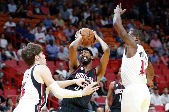 Houston Rockets forward Corey Brewer, center, looks for a shot around Miami Heat forward Luke Babbitt, left, and guard Dion Waiters during the first half of an NBA basketball game, Tuesday, Jan. 17, 2017, in Miami. (AP Photo/Wilfredo Lee)