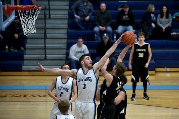 BRITTNEY LOHMILLER | blohmiller@mdn.net Meridian's Matt Hall blocks Bullock Creek's Josh Zastrow's shot in the second half of the Tuesday evening game. Meridian defeated Bullock Creek 52-38.