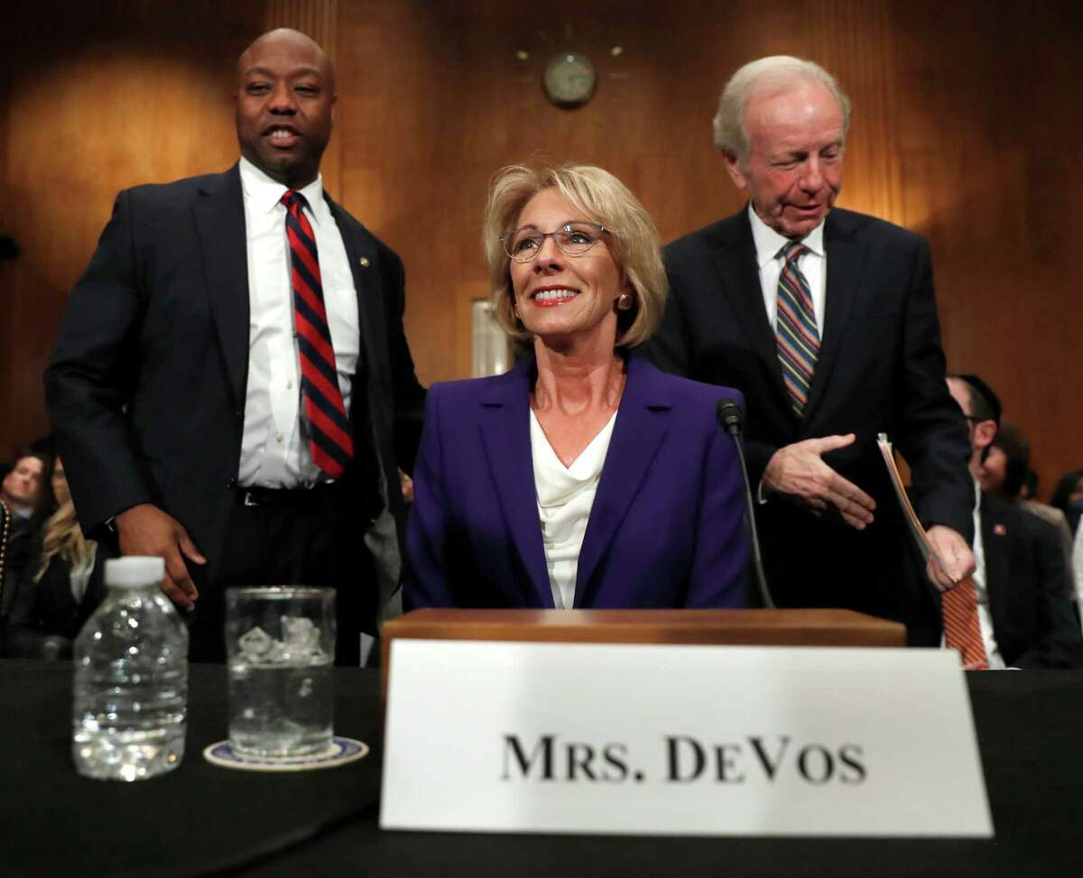 Education Secretary-designate Betsy DeVos arrives with former Sen. Joe Lieberman and Sen. Tim Scott, R-S.C., before testifying on Capitol Hill in Washington, Tuesday, Jan. 17, 2017, at her confirmation hearing before the Senate Health, Education, Labor and Pensions Committee. (AP Photo/Carolyn Kaster)