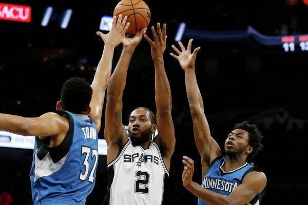 Spurs' Kawhi Leonard (02) scores against Minnesota Timberwolves' Karl-Anthony Towns (32) and Andrew Wiggins (22) during their game at the AT&T Center on Tuesday, Jan. 17, 2017.