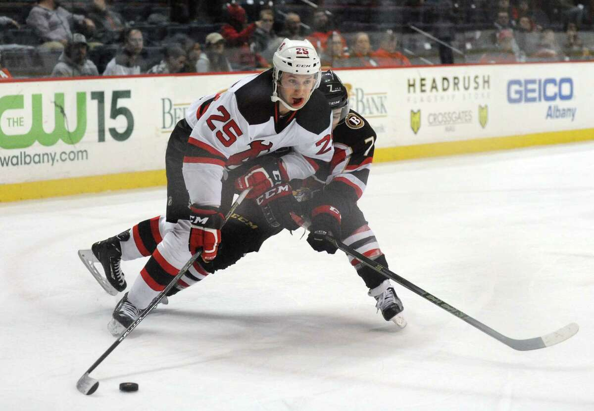 Devil Nick Lappin and Binghamton's Chris Carlisle go after the puck during their hockey game at the Times Union Center on Wednesday April 13, 2016 in Albany , N.Y. (Michael P. Farrell/Times Union) ORG XMIT: MER2017011716444602
