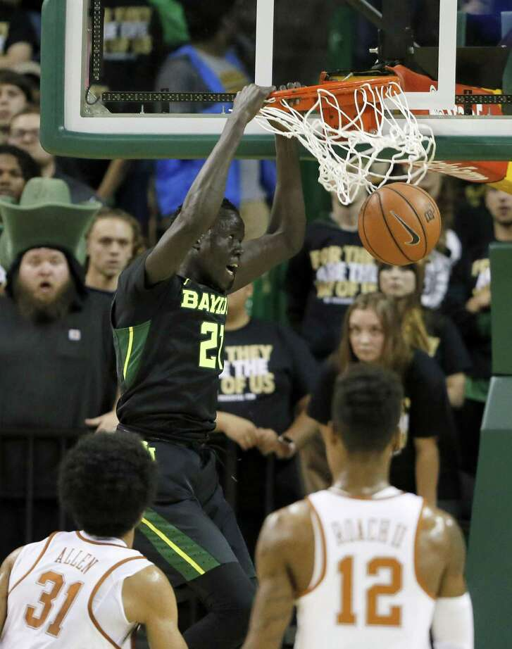 Baylor's Nuni Omot dunks as Texas' Jarrett Allen (left) and Kerwin Roach look on during the first half at the Ferrell Center.
