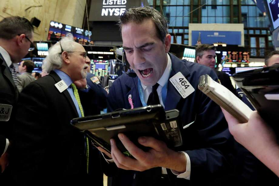 Trader Gregory Rowe, center, works on the floor of the New York Stock Exchange, Tuesday, Jan. 17, 2017. Stocks are opening slightly lower on Wall Street, led by declines in banks and health care companies. (AP Photo/Richard Drew) Photo: Richard Drew, STF / AP