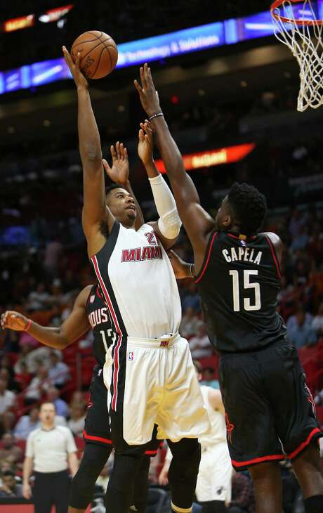 Clint Capela, right, challenges a shot by the Heat's Hassan Whiteside on Tuesday night in his first action for the Rockets since Dec. 17. Photo: David Santiago, MBR / Miami Herald