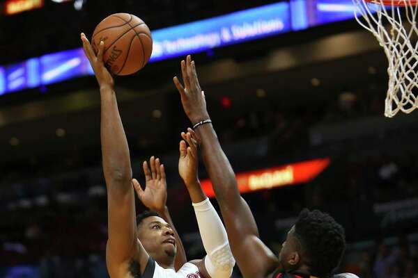 Clint Capela, right, challenges a shot by the Heat's Hassan Whiteside on Tuesday night in his first action for the Rockets since Dec. 17.