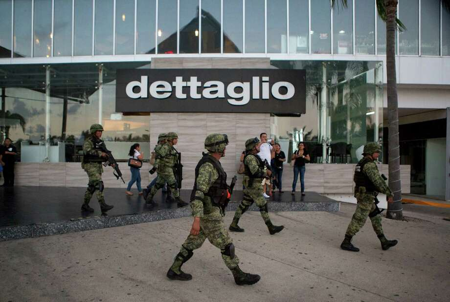Soldiers walk outside Plaza Las Americas mall following reports of gunfire in Cancun, Mexico, Tuesday, Jan. 17, 2017. Gunmen attacked the state prosecutor's office in this Caribbean resort city Tuesday, ratcheting up tensions just a day after a deadly shooting at a music festival in a nearby town. (AP Photo/Rebecca Blackwell) Photo: Rebecca Blackwell, STF / Copyright 2017 The Associated Press. All rights reserved.