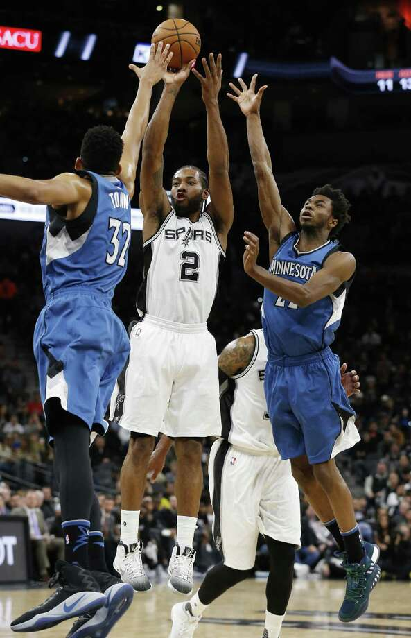 Spurs' Kawhi Leonard (02) scores against Minnesota Timberwolves' Karl-Anthony Towns (32) and Andrew Wiggins (22) during their game at the AT&T Center on Tuesday, Jan. 17, 2017. (Kin Man Hui/San Antonio Express-News) Photo: Kin Man Hui, Staff / San Antonio Express-News / ©2017 San Antonio Express-News