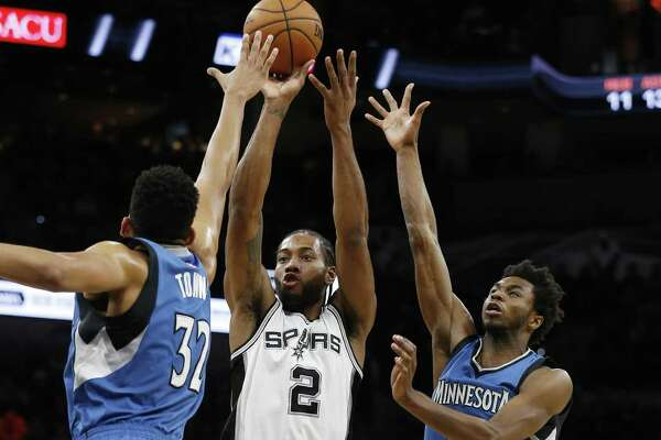 Spurs' Kawhi Leonard (02) scores against Minnesota Timberwolves' Karl-Anthony Towns (32) and Andrew Wiggins (22) during their game at the AT&T Center on Tuesday, Jan. 17, 2017. (Kin Man Hui/San Antonio Express-News)