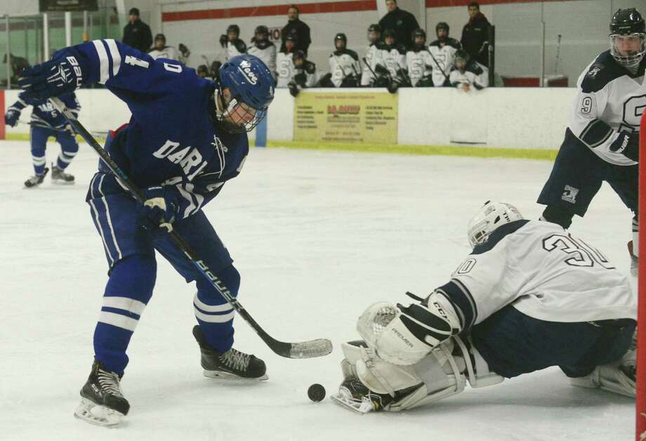 #4 for Darien High School, CJ Hathaway, tries to get the puck past goalie Zack Bloom as the Staples Co-op team takes on Darien in their FCIAC ice hockey game at the Miilford Ice Pavilion  saturday january 14, 2017, in Milford, Conn. Photo: Erik Trautmann / Hearst Connecticut Media / Connecticut Post