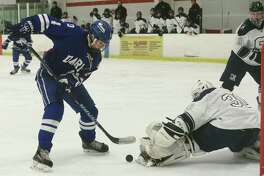 #4 for Darien High School, CJ Hathaway, tries to get the puck past goalie Zack Bloom as the Staples Co-op team takes on Darien in their FCIAC ice hockey game at the Miilford Ice Pavilion  saturday january 14, 2017, in Milford, Conn.