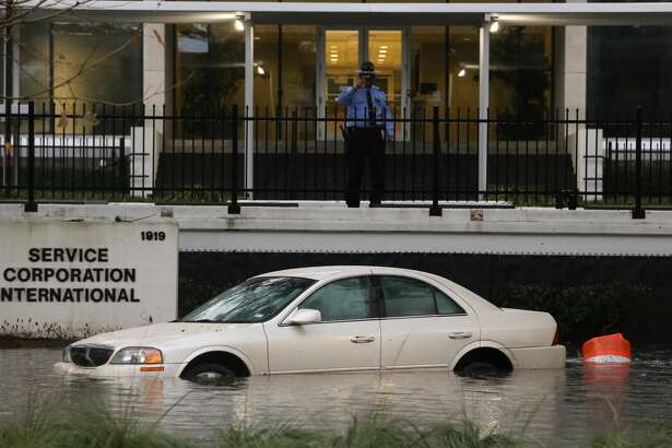 A guard at Service Corporation International takes a photo of a car submerged under water in front of its building due to the storm Wednesday morning, January 18, in Houston. (Yi-Chin Lee/ Houston Chronicle)