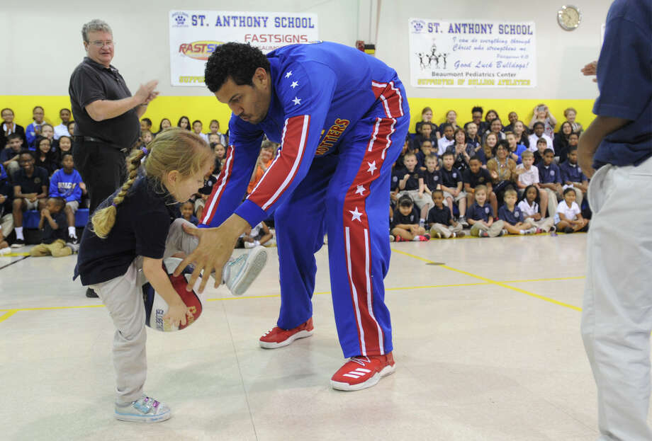 The Harlem Globetrotter's Orlando Melendez helps Margeaux Stevens handle the ball under her leg during a basketball exhibit at St Anthony Cathedral School on Tuesday. The event was designed to teach kids about bullying.  Photo taken Tuesday, January 17, 2017 Guiseppe Barranco/The Enterprise Photo: Guiseppe Barranco, Photo Editor