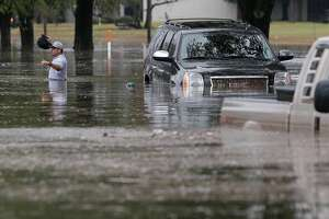 A man walks from his flooded SVU after getting stranded along Stancliff near 59 and West Bellfort Wednesday, Jan. 18, 2017. ( Melissa Phillip/ Houston Chronicle)