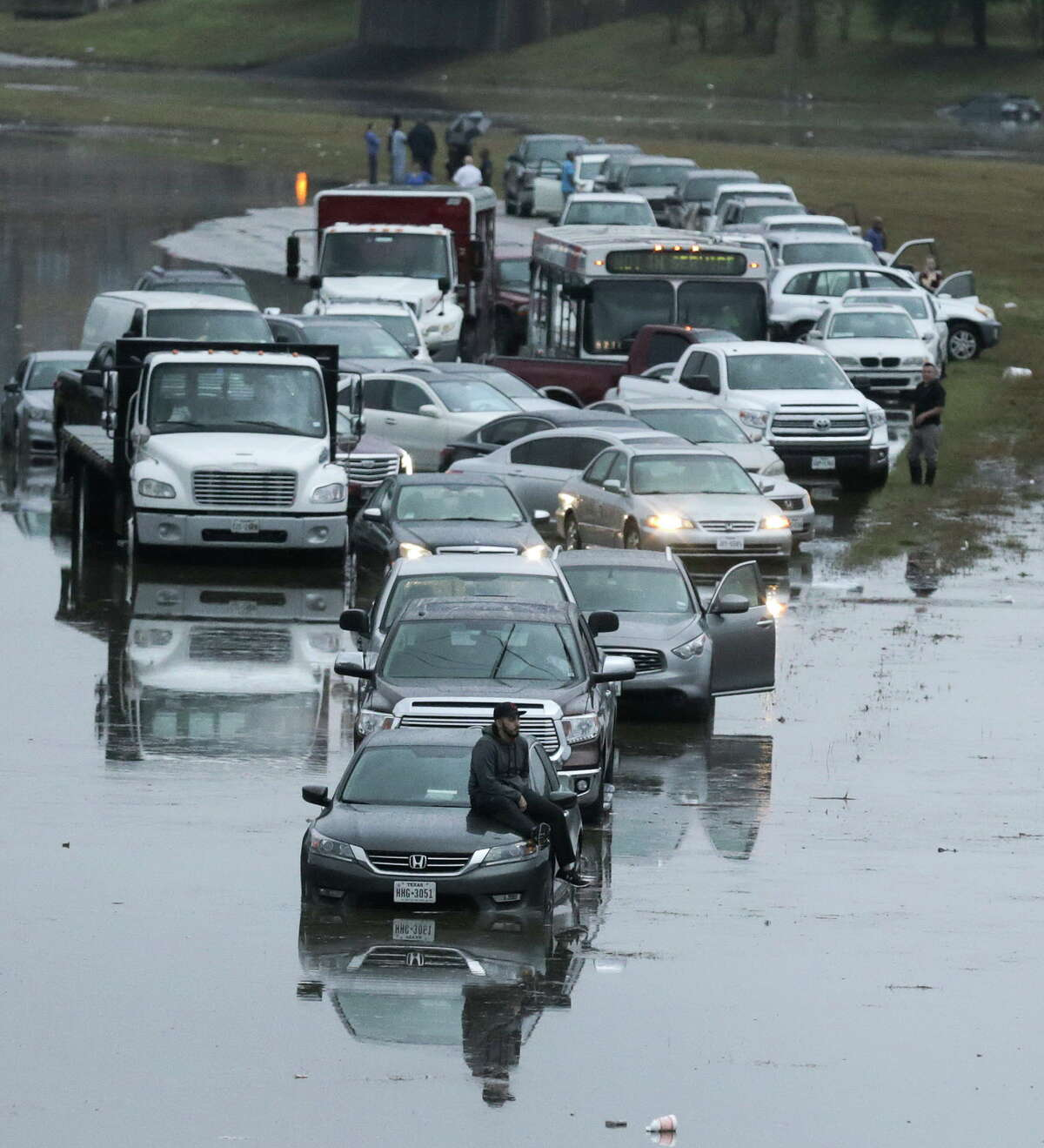 People wait for the water to recede on northbound 288 near Calumet after getting stuck flooding from the bayou after heavy nightfall rain on Wednesday, Jan. 18, 2017, in Houston.