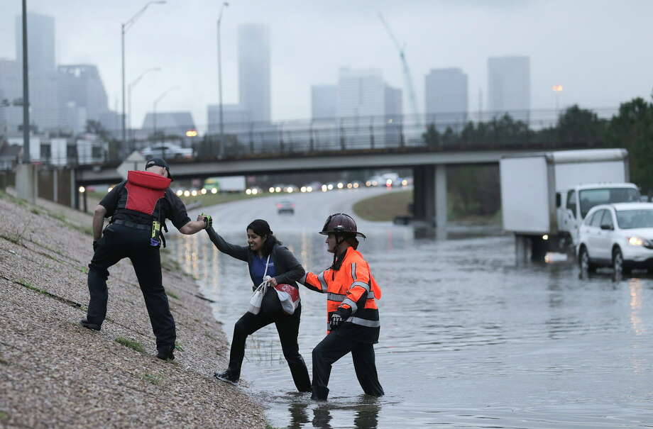 Emergency workers help a woman out of 288. Photo: Elizabeth Conley, Houston Chronicle / © 2017 Houston Chronicle