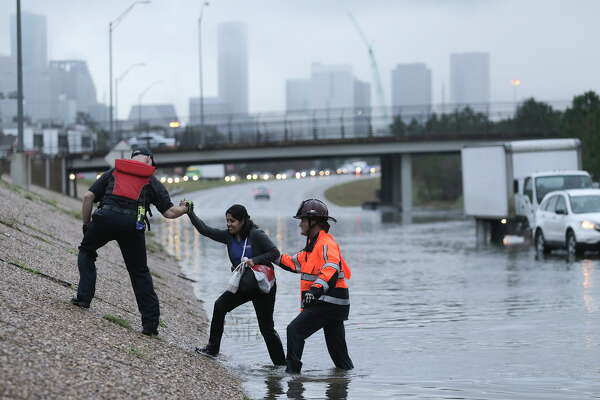 A woman is helped out of a flooded 288 on Wednesday, Jan. 18, 2017, in Houston.