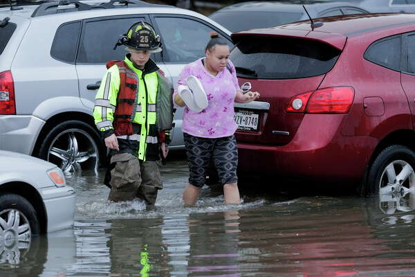 A Houston firefighter helps a woman out of her car on a flooded 288  on Wednesday, Jan. 18, 2017, in Houston.