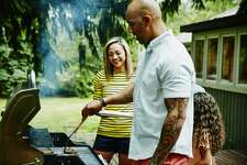 Family cooking burgers on barbecue in backyard on summer evening