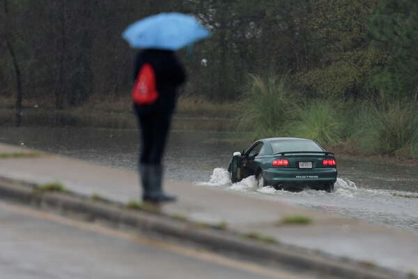 A Mustang tries to make its way opposite traffic on southbound 288 after being stuck in the flooded freeway  on Wednesday, Jan. 18, 2017, in Houston.