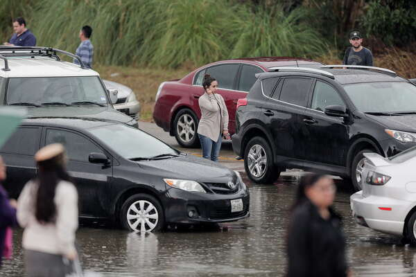 People wait for the water to recede on southbound 288 near Calumet after getting stuck flooding from the bayou after heavy nightfall rain on Wednesday, Jan. 18, 2017, in Houston.