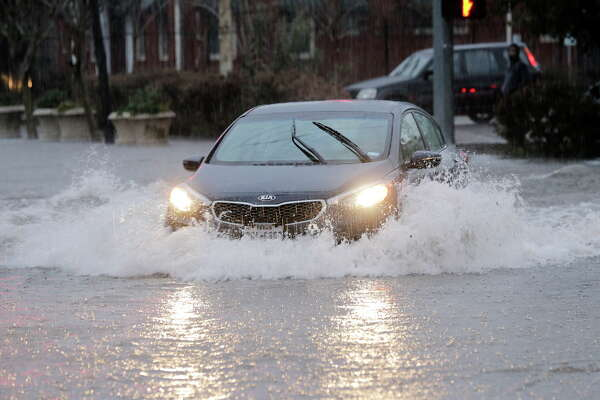 A Kia sedan makes its way onto San Jacinto street through the flooded intersection  on Wednesday, Jan. 18, 2017, in Houston.