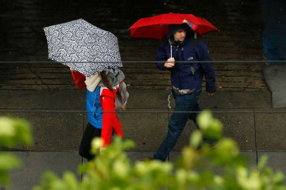 Pedestrians make their way through downtown during a rainy day on Saturday, Dec. 10, 2016 in San Francisco, Calif.