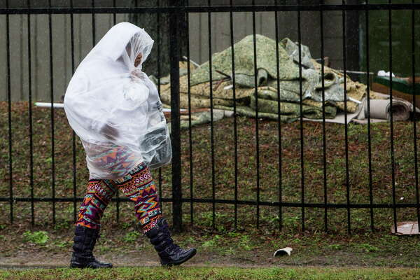 A pedestrian is covered with a plastic bag while walking along Greens Road next to the Arbor Court Apartments, which were flooded last April, on Wednesday, Jan. 18, 2017, in Houston.
