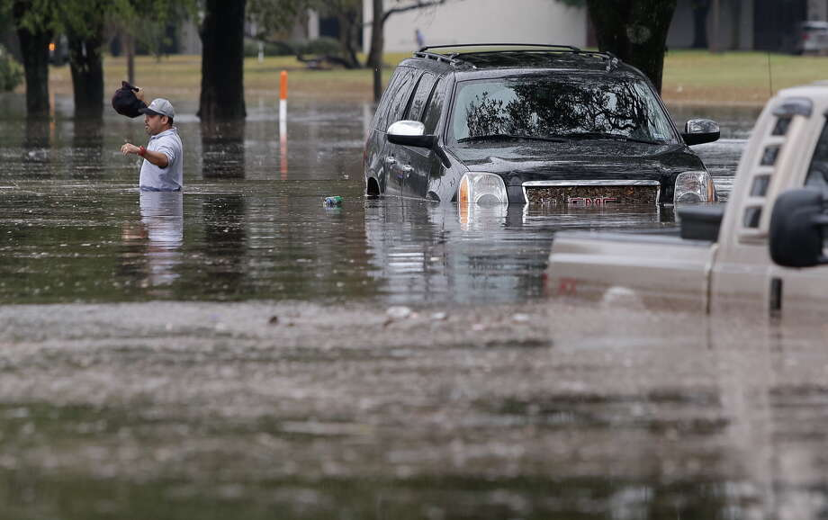 A man walks from his flooded SUV after getting stranded along Stancliff near 59 and West Bellfort Wednesday, Jan. 18, 2017. ( Melissa Phillip/ Houston Chronicle) Photo: Melissa Phillip / Houston Chronicle 2017
