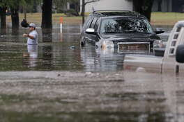 A man walks from his flooded SUV after getting stranded along Stancliff near 59 and West Bellfort Wednesday, Jan. 18, 2017. ( Melissa Phillip/ Houston Chronicle)
