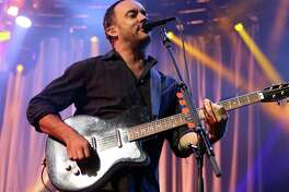 FILE - In this June 28, 2013 file photo, Dave Matthews of The Dave Matthews Band performs on stage at the Susquehanna Bank Center in Camden, N.J. Emily Kraus , one of Matthew's fans pulled over to give a stranded cyclist a ride and realized the hitchhiker was none other than Matthews. His bike had broken down Saturday, July 13, before a show in Hershey, Pa.  (Photo by Owen Sweeney/Invision/AP, File)
