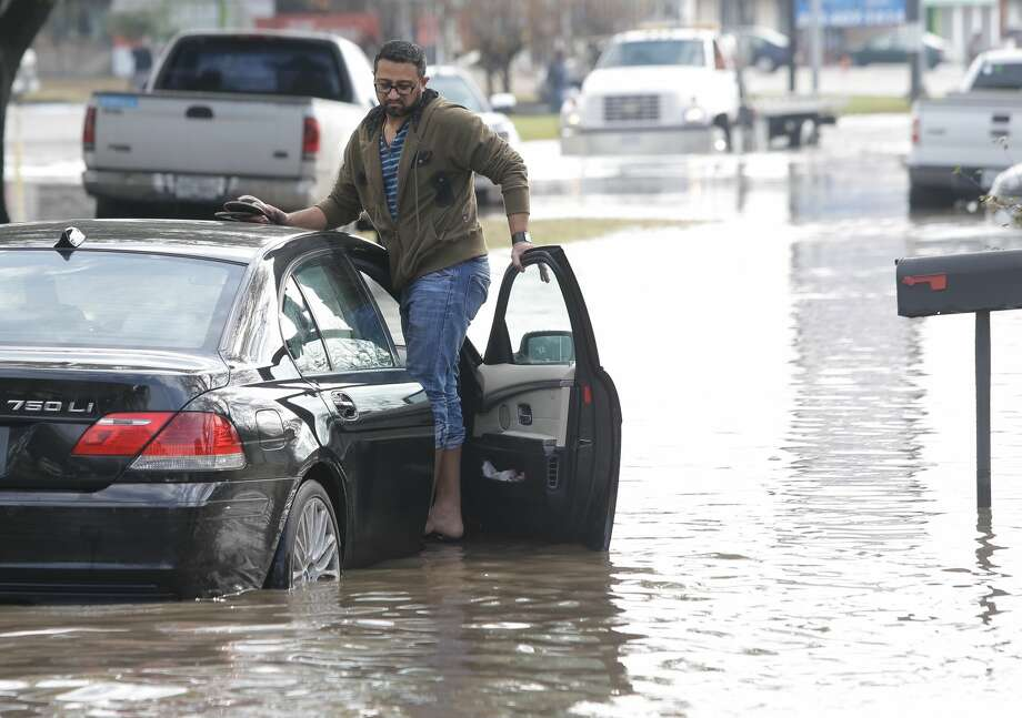 Syed Ali waits with his stranded car, at West Bellfort at 59. Photo: Melissa Phillip | Houston Chronicle