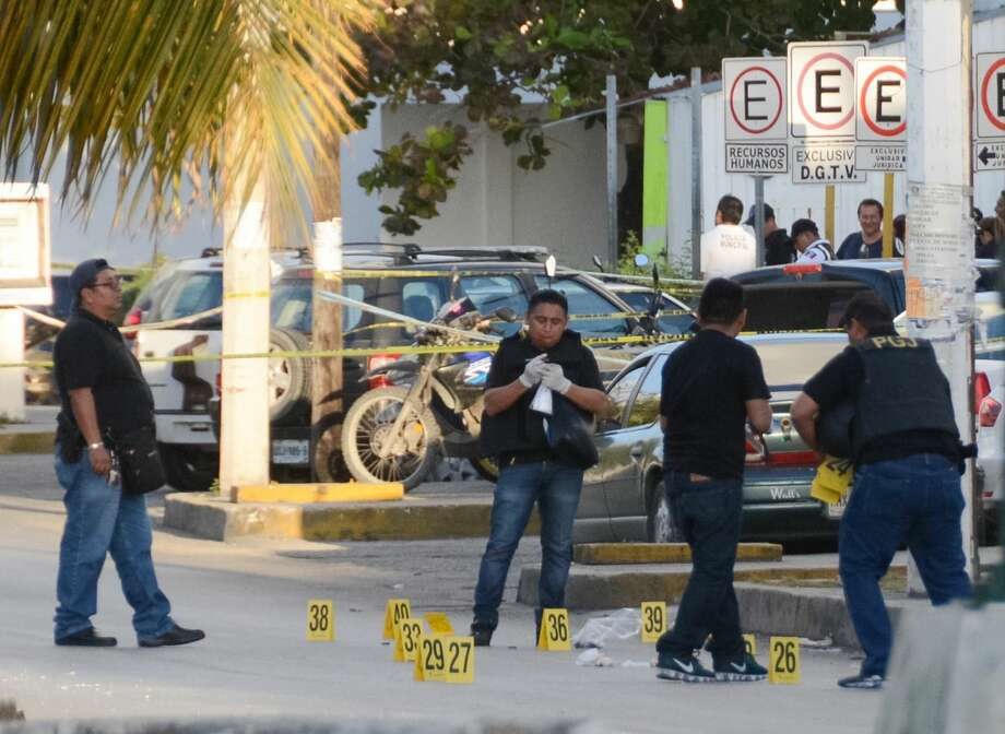 FILE — Police investigators work on the crime scene where a shooting erupted after an attack against the building of the Quintana Roo State Prosecution, in Cancun, Mexico, on January 17, 2017. On Monday, March 5, 2018, officials said four gunmen burst into a hospital in the Mexican resort of Cancun and 